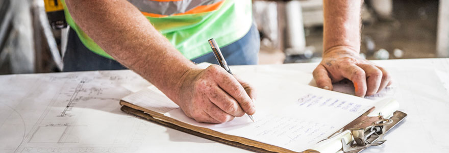 Une homme faisant une liste de tâches à réaliser pour son chantier.